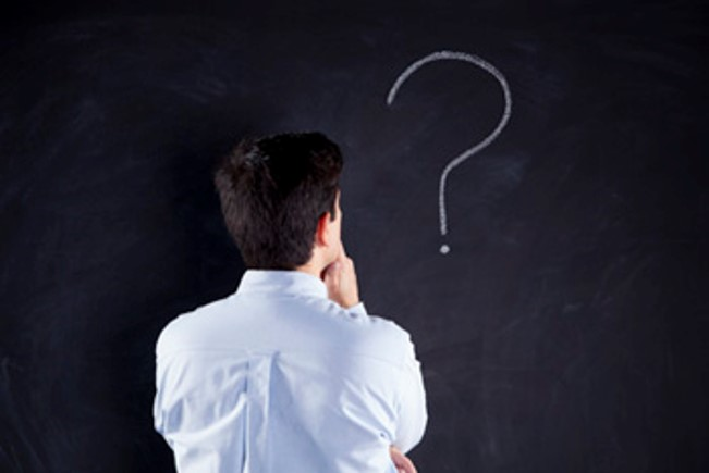 a man staring at a question mark drawn on a chalkboard